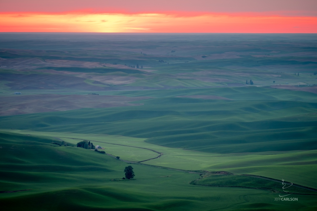 The sun turns crimson at the end of the day over Palouse farmland as seen from Steptoe Butte.
