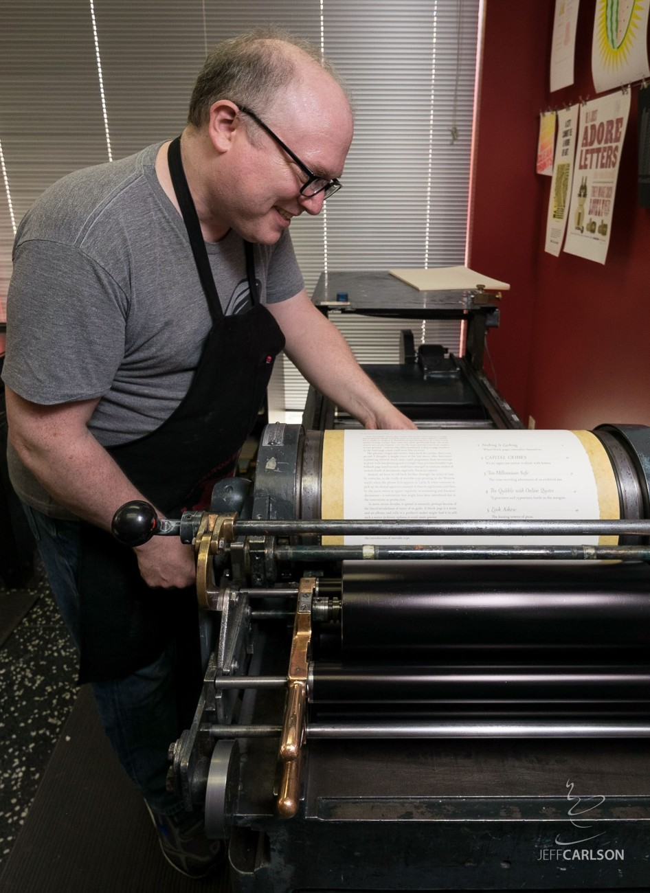 Fleishman cranks the print assembly across photopolymer plates to make an impression on a page.