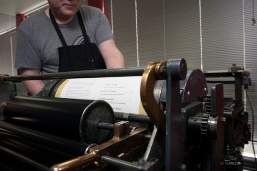 A freshly-inked sheet at the end of its impression on a vintage Vandercook proof press.